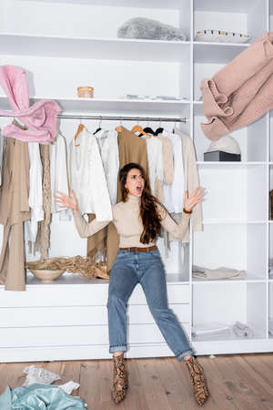 Photo pour Angry woman throwing clothes while sitting on shelf in wardrobe - image libre de droit