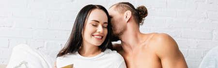 Photo pour Muscular man kissing smiling woman in bedroom, banner - image libre de droit