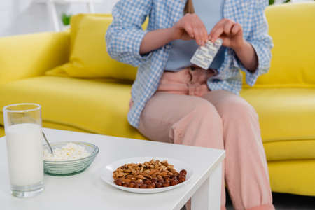 Photo pour Cropped view of nuts, cottage cheese and milk on table near woman with allergy holding pills on blurred background - image libre de droit