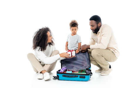 Photo pour african american woman holding gift box near suitcase and family on white - image libre de droit