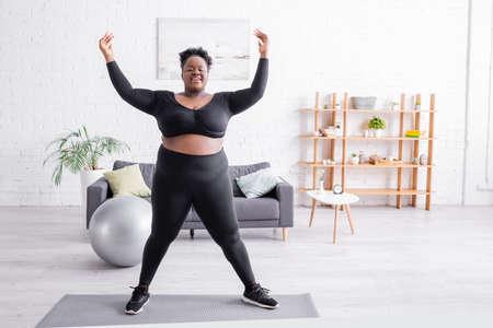 Foto für full length of cheerful african american plus size woman in sportswear training on fitness mat - Lizenzfreies Bild