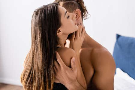 Photo pour Brunette woman touching neck of shirtless boyfriend on blurred background - image libre de droit