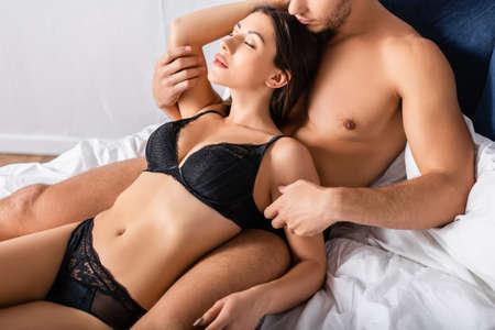 Photo pour Passionate woman lying near muscular boyfriend on bed - image libre de droit
