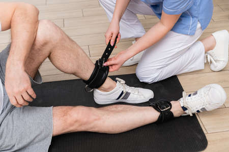 Photo pour cropped view of trainer fastening leather belt on leg of man in rehabilitation center - image libre de droit