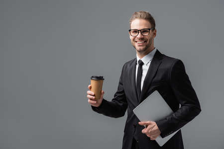 Photo pour happy businessman with takeaway drink and laptop smiling at camera isolated on gray - image libre de droit