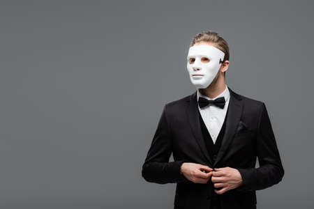 Photo for businessman in face mask buttoning blazer isolated on gray - Royalty Free Image