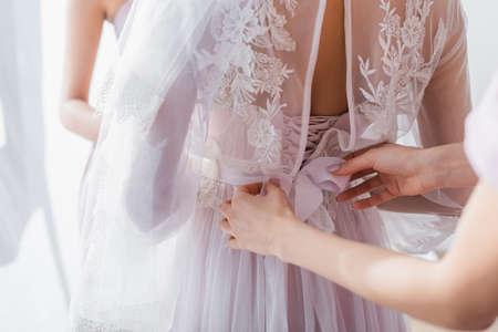 Foto für partial view of bridesmaid tying ribbon on lace dress of bride - Lizenzfreies Bild