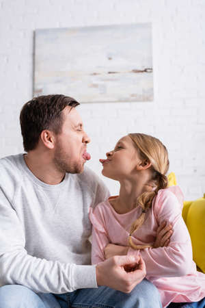 Photo pour father and daughter sticking out tongues while having fun at home - image libre de droit