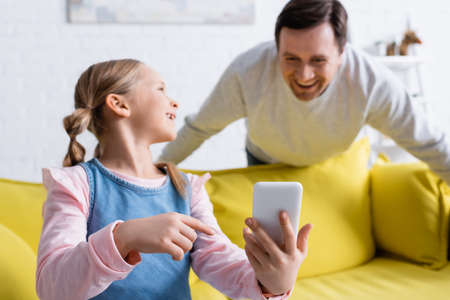 Photo for smiling girl pointing at mobile phone near father laughing on blurred background - Royalty Free Image
