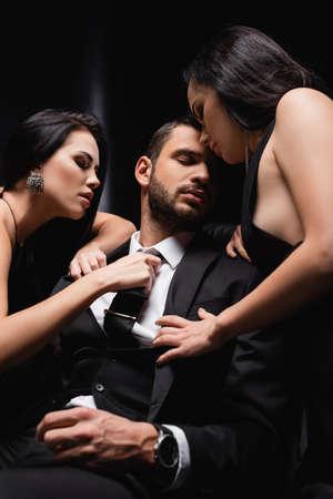 Photo pour sensual women undressing businessman in suit on black - image libre de droit