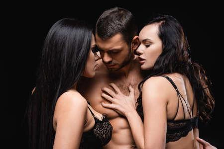 Photo pour sexy man near seductive, brunette women seducing him isolated on black - image libre de droit