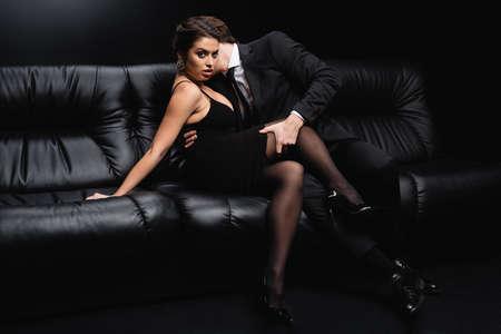 Photo pour man in suit seducing sexy woman in slip dress sitting on sofa on black - image libre de droit