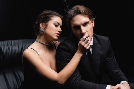 Photo pour seductive woman holding cigarette near man in suit isolated on black - image libre de droit