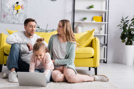 Photo for Child using laptop near excited parents on floor at home - Royalty Free Image