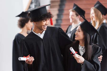 Photo pour African american graduate hugging asian friend with diploma - image libre de droit