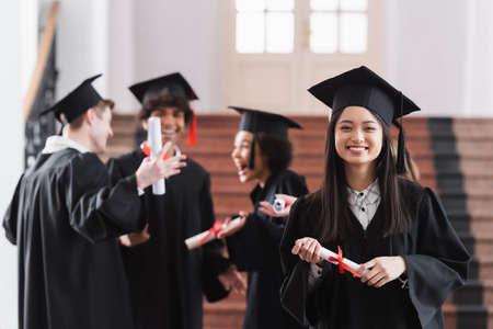 Photo pour Asian bachelor smiling at camera near blurred friends in university - image libre de droit