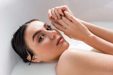Photo pour pretty woman holding hands near face while relaxing in bath with milk - image libre de droit