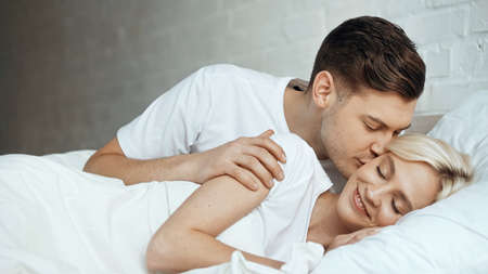 Photo for happy man kissing blonde woman lying with closed eyes in bed - Royalty Free Image
