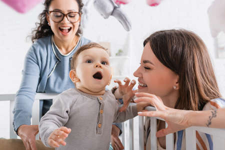 Photo pour smiling mother gesturing near amazed infant son in baby crib and excited african american friend - image libre de droit