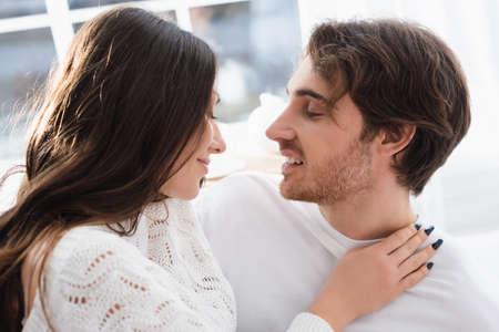 Foto de Side view of smiling woman hugging boyfriend at home - Imagen libre de derechos