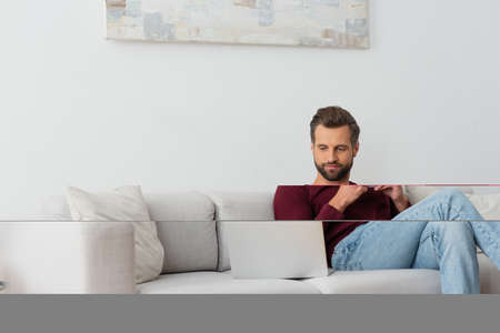 Photo pour man with cup of coffee sitting on sofa near laptop - image libre de droit