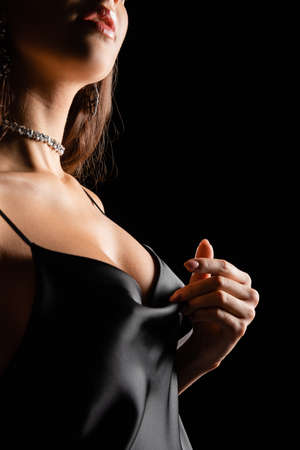 Photo pour cropped view of sensual woman in silk dress touching breast with hand isolated on black - image libre de droit