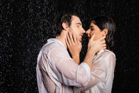 Photo pour passionate sexy couple in wet clothes standing in rain drops on black background - image libre de droit