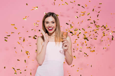 Photo pour Pretty woman with champagne looking at camera near golden confetti during party on pink background - image libre de droit