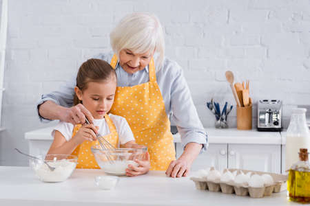 Photo pour Granny and kid cooking together near ingredients in kitchen - image libre de droit