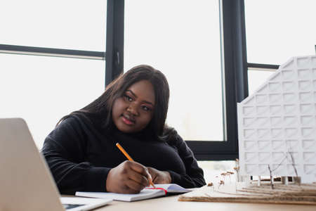 Photo for african american plus size designer writing in notebook while looking at laptop near house model - Royalty Free Image