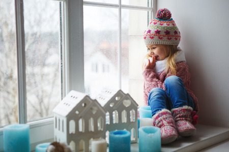 Photo pour little girl on a window sill looks at the street - image libre de droit