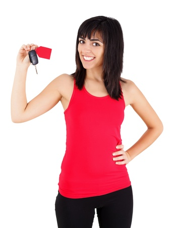 Confident young woman smiling happily with a new car key with tag in her hands - isolated on white.