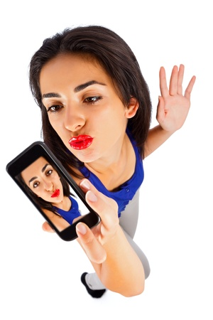 Beautiful girl making duck face taking selfportrait with her smart phone.