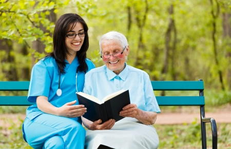 Caring doctor with kind elderly lady sitting on a bench reading a book.