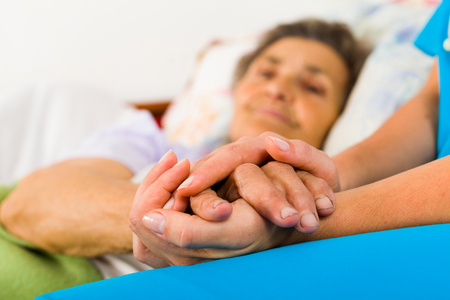 Foto de Caring nurse holding kind elderly lady's hands in bed. - Imagen libre de derechos
