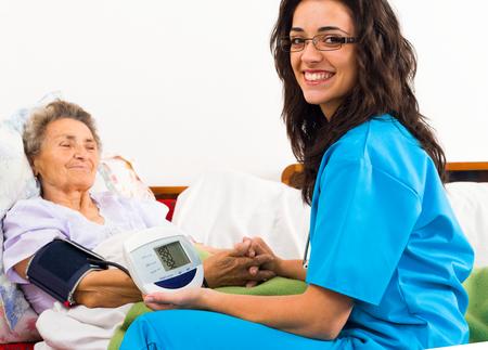 Nurse using digital blood pressure for senior patient.