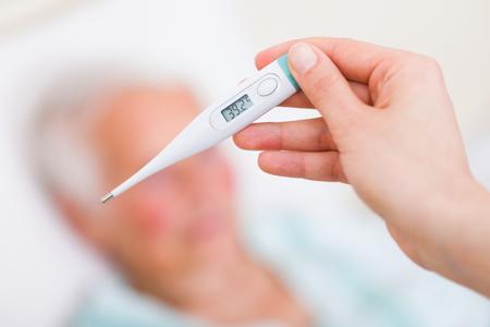 Nurse checkin sick patient's body temperature - fever.