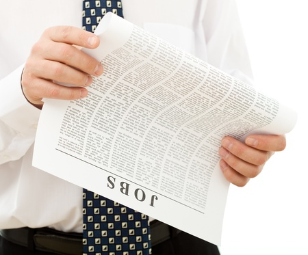Man in shirt and tie looking for job reading a paper with clasified ads - closeup, isolated