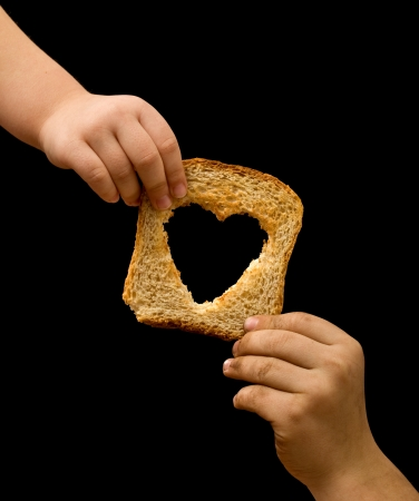 Photo pour Sharing food with the needy - kids hands with a slice of bread - image libre de droit