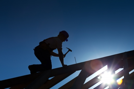Photo pour Builder or carpenter working on the roof - silhouette with strong back light - image libre de droit