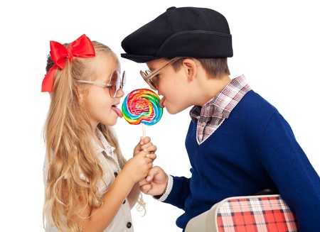 Photo pour Love is sharing - childhood sweethearts with a lollipop and vintage clothes - image libre de droit
