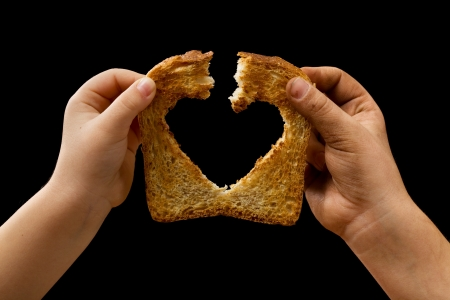 Photo pour Sharing food with love - kids hands breaking a slice of bread - image libre de droit