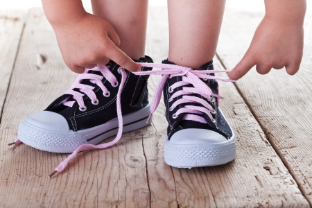 Child successfully ties shoes - closeup on feet and hands