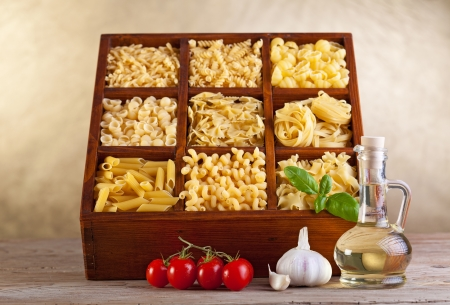 Assorted pasta mix in wooden box and seasoning ingredients
