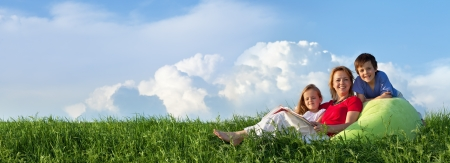 Photo for Family relaxing outdoors in the fresh spring grass - panorama - Royalty Free Image