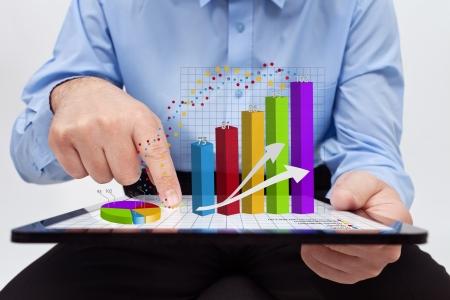 Foto de Businessman editing the annual report charts - working on a tablet computer - Imagen libre de derechos