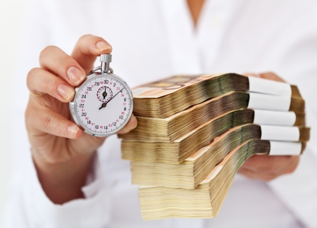 Limited time offer concept with stack of money and stopwatch in woman hands - shallow depth