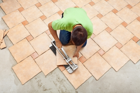 Man laying ceramic floor tiles working with a cutter device - top view