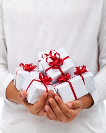 Lots of christmas presents in child hands - thankfulness for abundance concept, with copy space