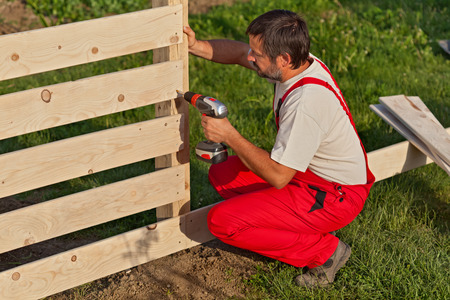 Man building a wooden fence - fastening the boards with screws